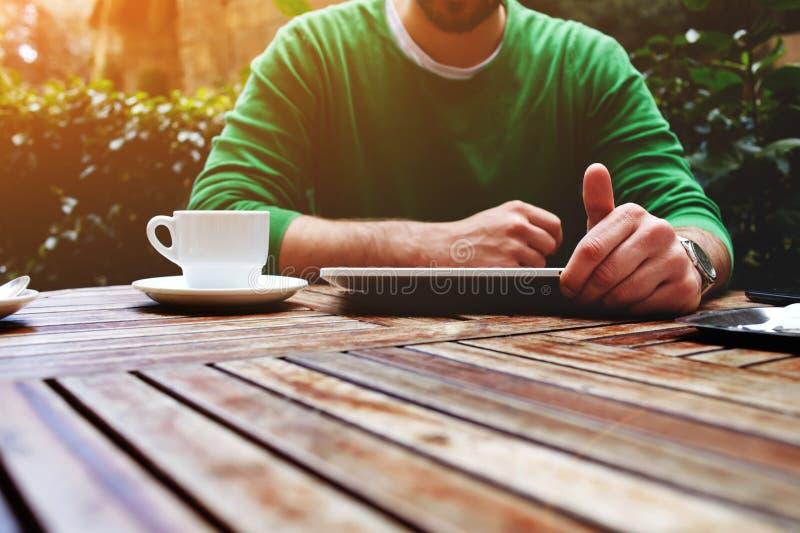Las manos del hombre que mandan un SMS al mensaje en la tableta de la pantalla táctil mientras que se sienta en la terraza con la fotos de archivo libres de regalías