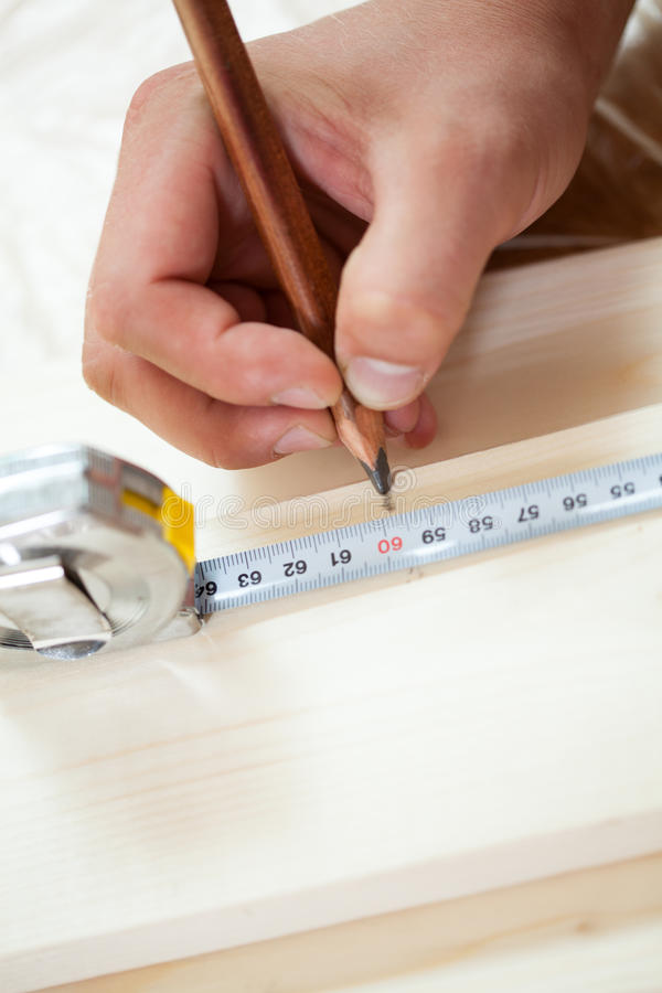 Las manos del hombre que miden la longitud del tablero fotografía de archivo