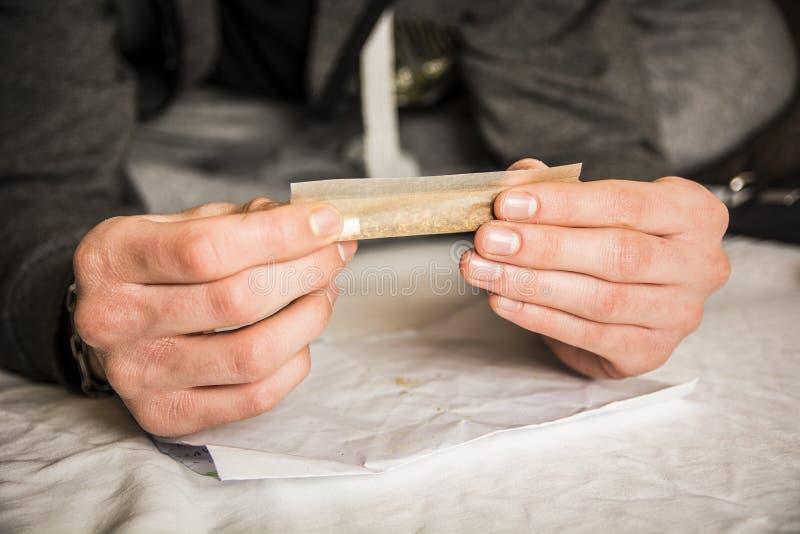 Las manos del hombre que ruedan el cigarrillo fotografía de archivo