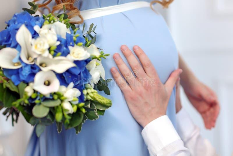 Las manos del hombre que tocan el estómago su mujer embarazada foto de archivo libre de regalías