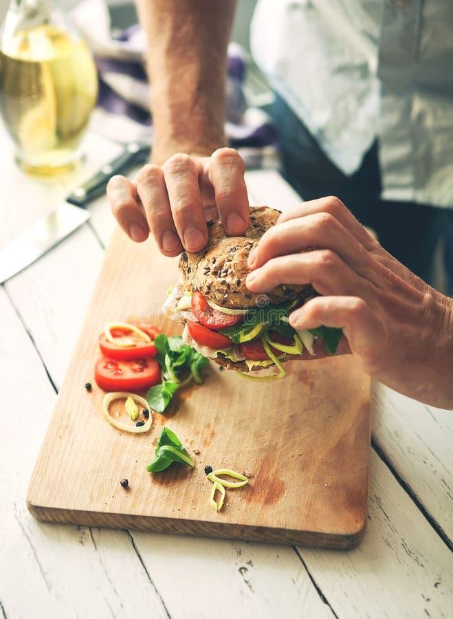 Las manos del hombre toman un bocadillo con el jamón y las verduras fotografía de archivo libre de regalías