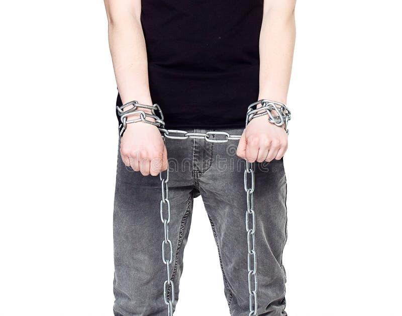 Las manos del hombre y cadenas del hierro El concepto de esclavitud imagenes de archivo