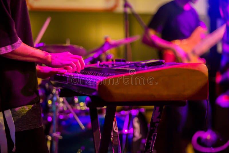 Las manos del músico que juegan el teclado en una demostración viva en etapa con otros hombres que tocan las guitarras foto de archivo
