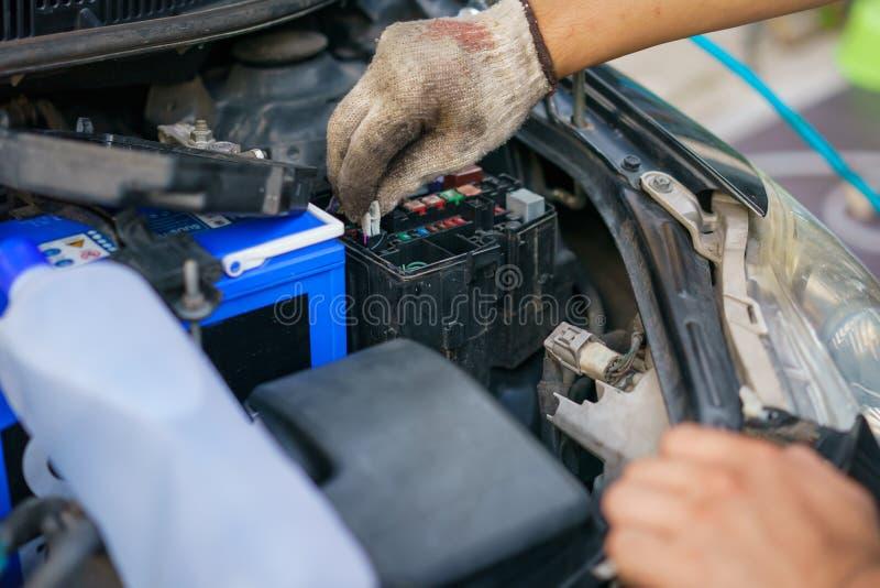Las manos del mecánico que substituye el fusible en el coche El mecánico selecciona el fusible correcto Foco selectivo imágenes de archivo libres de regalías