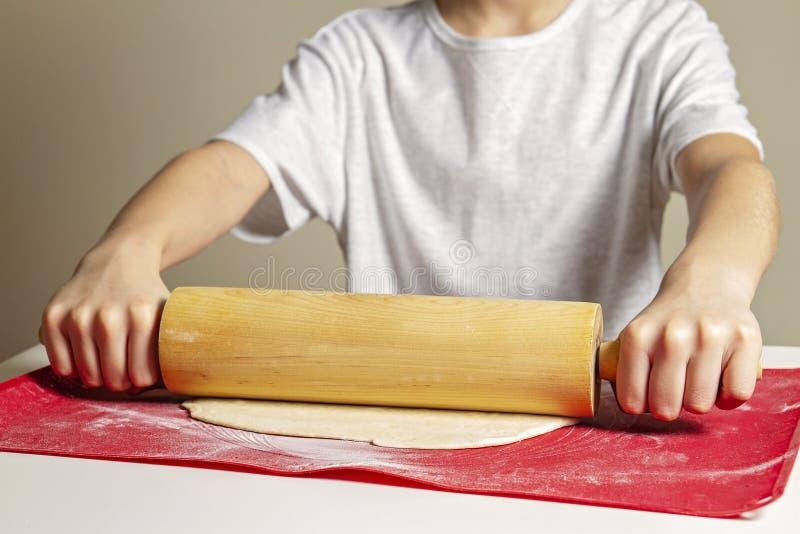 Las manos del niño desarrollan la pasta de la pizza con el rodillo en el balanceo de la pasta del silicón y la estera que cuece fotos de archivo
