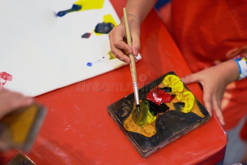 Las manos del niño están coloreando el sello para hacer actividad de las ilustraciones fotos de archivo