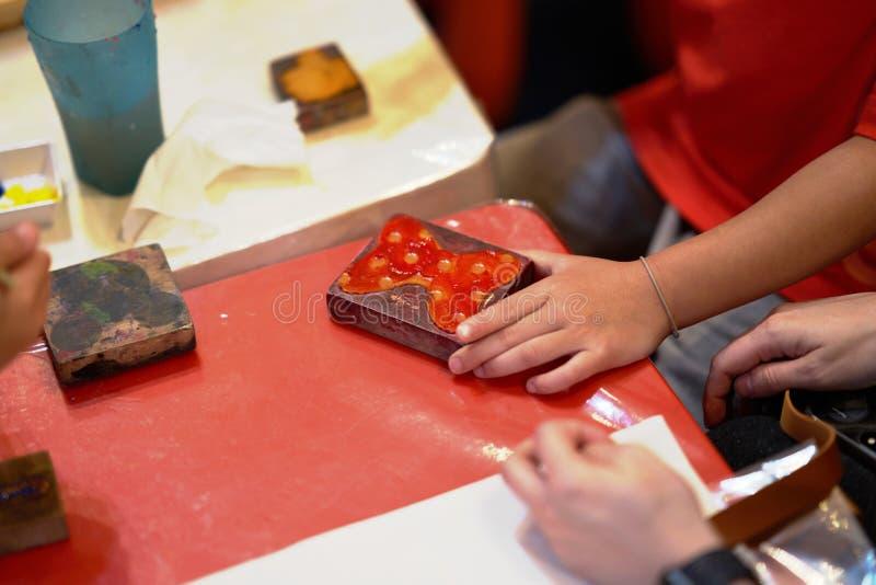 Las manos del niño están coloreando el sello para hacer actividad de las ilustraciones imagen de archivo libre de regalías
