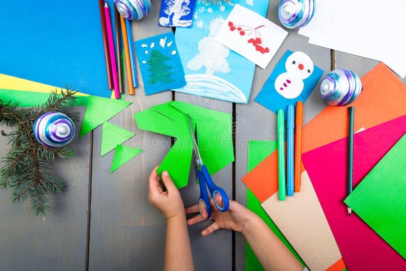 Las manos del niño hacen los juguetes hechos a mano de la Navidad de la cartulina Concepto del DIY de los niños imagen de archivo libre de regalías