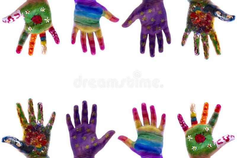 Las manos del niño pintaron la acuarela en el fondo blanco imágenes de archivo libres de regalías