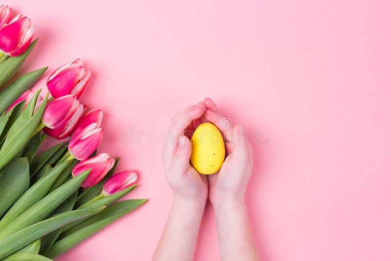 Las manos del niño sostienen el huevo de Pascua Fondo del día de fiesta de Pascua con los tulipanes rosados de las flores y el es foto de archivo libre de regalías