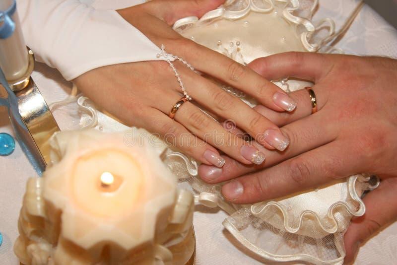 Las manos del novio y de la novia mienten encima de uno a fotografía de archivo libre de regalías