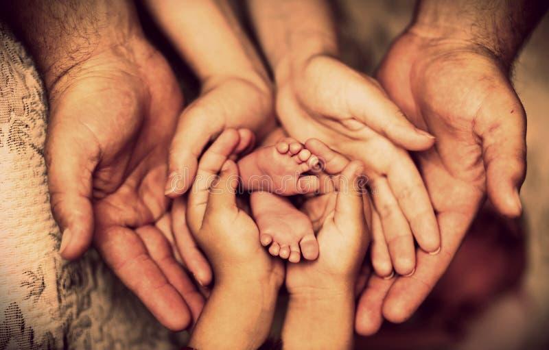 Las manos del padre, madre, hija guardan al pequeño bebé de los pies Familia feliz amistosa imagenes de archivo