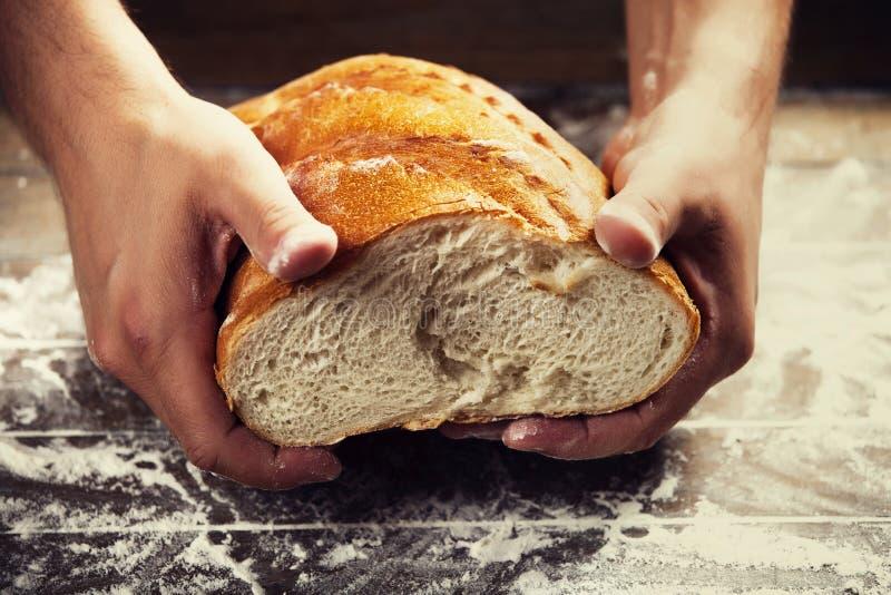 Las manos del panadero con un pan fotografía de archivo
