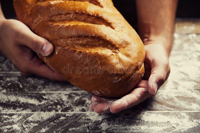 Las manos del panadero con un pan imagen de archivo