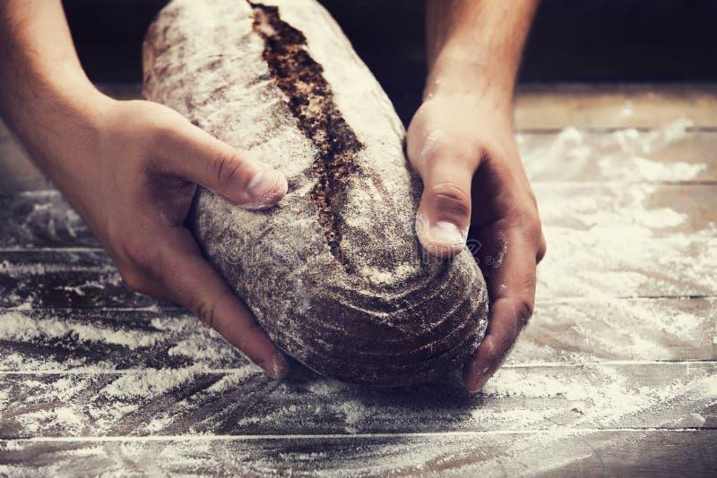 Las manos del panadero con un pan foto de archivo libre de regalías