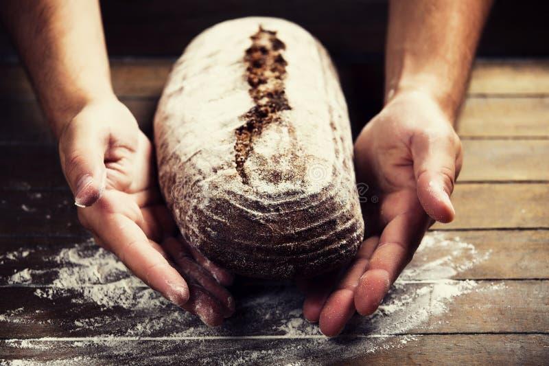 Las manos del panadero con un pan imágenes de archivo libres de regalías
