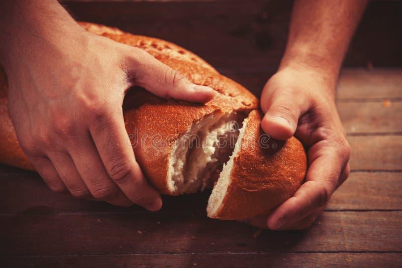 Las manos del panadero con un pan. imagen de archivo libre de regalías