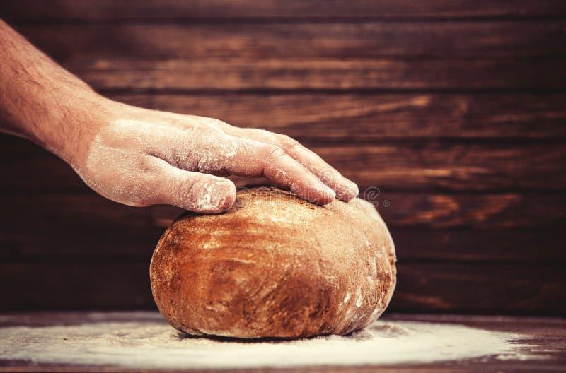 Las manos del panadero con un pan. fotos de archivo libres de regalías