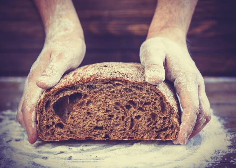 Las manos del panadero con un pan. imágenes de archivo libres de regalías