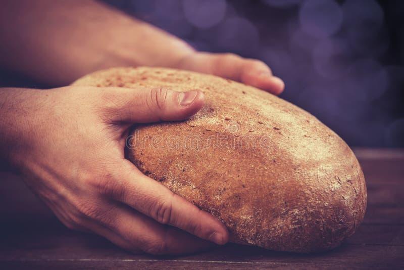 Las manos del panadero con un pan. fotos de archivo