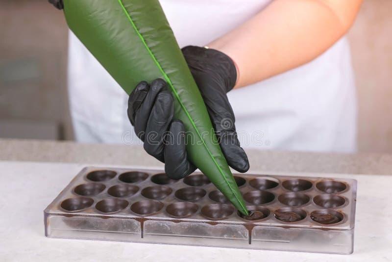 Las manos del panadero que vierten la almendra garapi?ada de relleno del chocolate l?quido en formulario del bolso de los pastele imagen de archivo