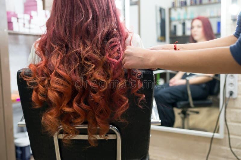 Las manos del peluquero hacen la formación de rizos del pelo largo en la cabeza del cliente en el salón fotografía de archivo libre de regalías
