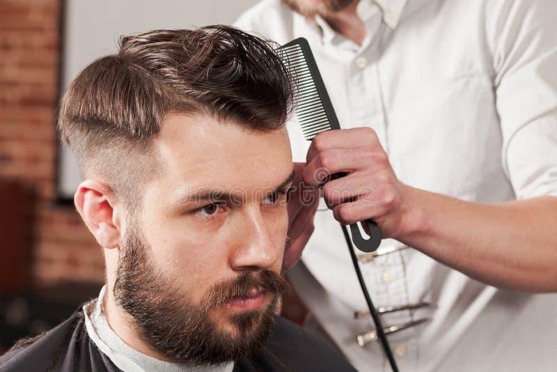 Las manos del peluquero que hacen corte de pelo al hombre joven en barbería imagenes de archivo