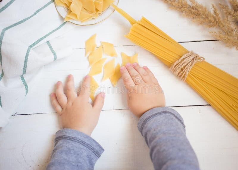 Las manos del pequeño bebé que sostienen las pastas en la tabla de madera blanca, cocinando con concepto de los niños fotos de archivo