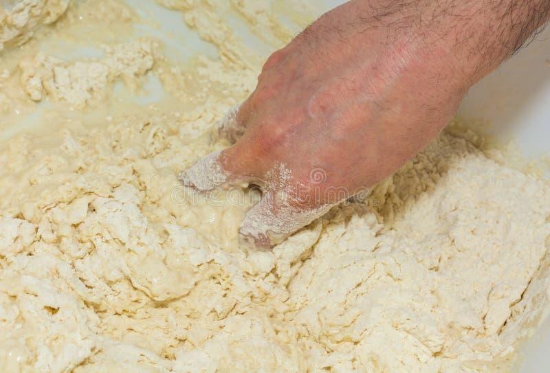Las manos del ` s del cocinero amasan la pasta para hacer la pizza en la cocina Comida, cocina italiana y concepto el cocinar Pre imagen de archivo