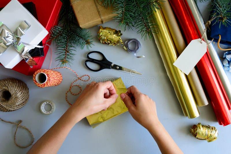 Las manos del ` s de la mujer adornan la actual caja en fondo de madera gris Concepto de las decoraciones del Año Nuevo y de la N imágenes de archivo libres de regalías