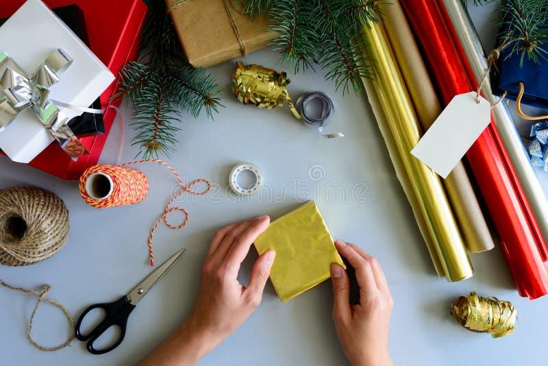 Las manos del ` s de la mujer adornan la actual caja en fondo de madera gris Concepto de las decoraciones del Año Nuevo y de la N fotos de archivo libres de regalías