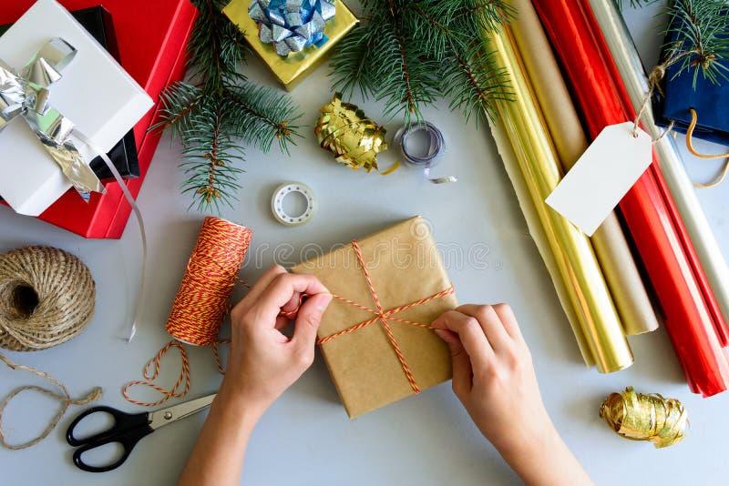 Las manos del ` s de la mujer adornan la actual caja en fondo de madera gris Concepto de las decoraciones del Año Nuevo y de la N fotografía de archivo libre de regalías