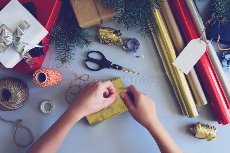 Las manos del ` s de la mujer adornan la actual caja en fondo de madera gris Concepto de las decoraciones del Año Nuevo y de la N imagenes de archivo