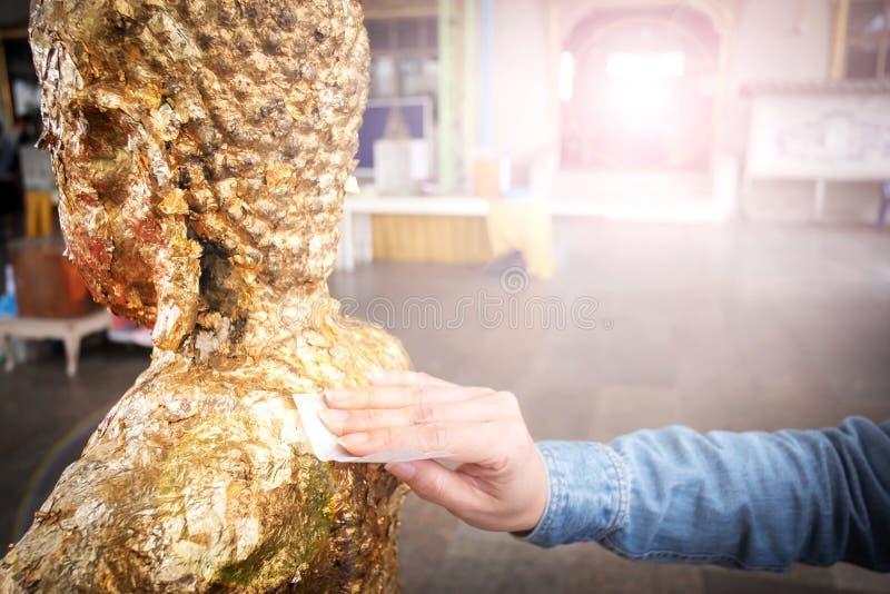 Las manos del ` s de la mujer doran detrás de la estatua de Buda imagen de archivo