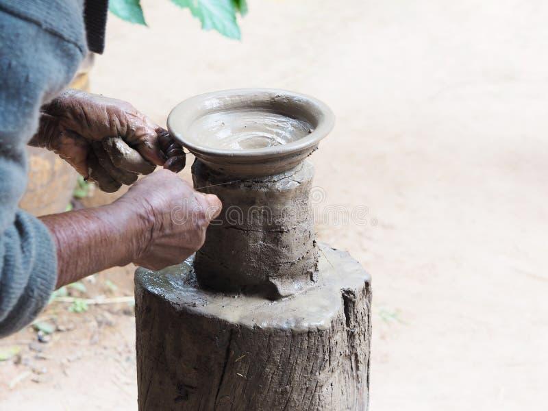 Las manos del ` s de la mujer mayor esculpen la cerámica de la arcilla en soporte de madera fotografía de archivo libre de regalías