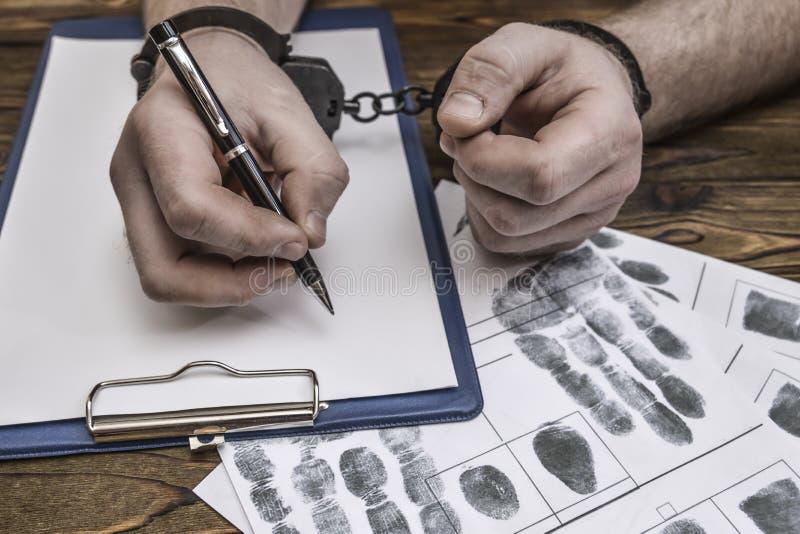 Las manos del ` s de los hombres con las esposas llenan el expediente de la policía, confesión imagenes de archivo
