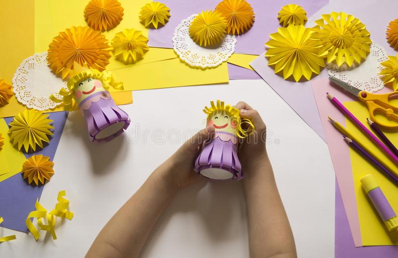 Las manos del ` s de los niños hacen a una princesa del papel Práctico para un partido fotografía de archivo libre de regalías