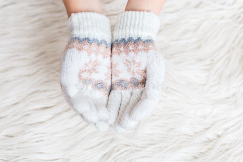 Las manos del ` s de los niños del invierno son blancas en manoplas en un fondo blanco de la piel hygge Las manos se están sosten fotos de archivo libres de regalías