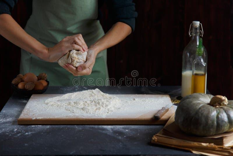 Las manos del ` s de las mujeres amasan la pasta Ingredientes de la hornada en la tabla de madera fotos de archivo libres de regalías
