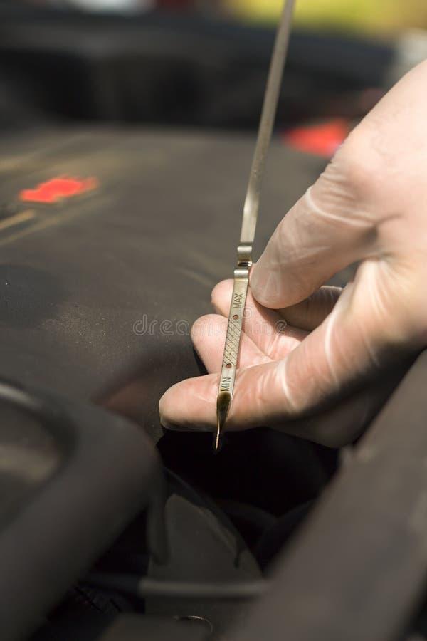 Las manos del ` s del hombre en guantes disponibles comprueban el nivel de aceite en el motor foto de archivo