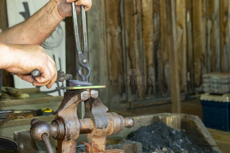 Las manos del ` s del herrero en el trabajo en la fragua que trabajaba con el objeto se sostuvieron en tornillo con las pinzas en foto de archivo
