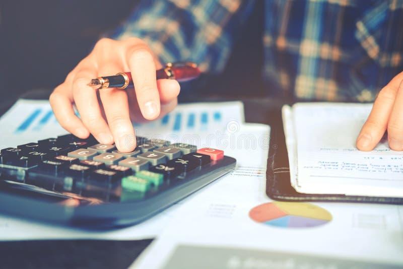 Las manos del ` s del hombre de negocios con la calculadora en la oficina y los datos financieros costaron económico imagen de archivo libre de regalías