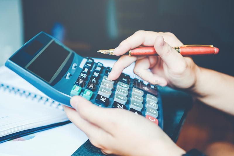 Las manos del ` s del hombre de negocios con la calculadora en la oficina y los datos financieros costaron económico fotos de archivo libres de regalías