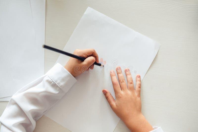 Las manos del ` s del ni?o se pintan con los l?pices coloreados en una hoja de papel blanca en una tabla de madera foto de archivo