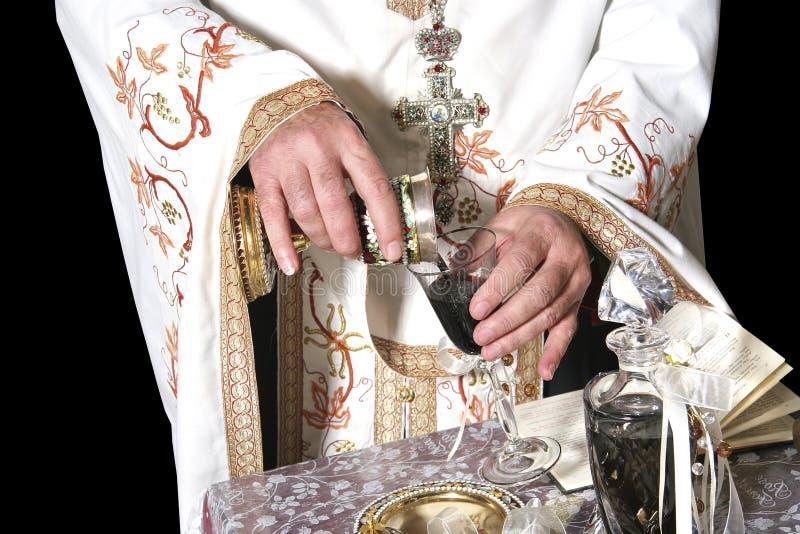 Las manos del sacerdote con el vino fotos de archivo