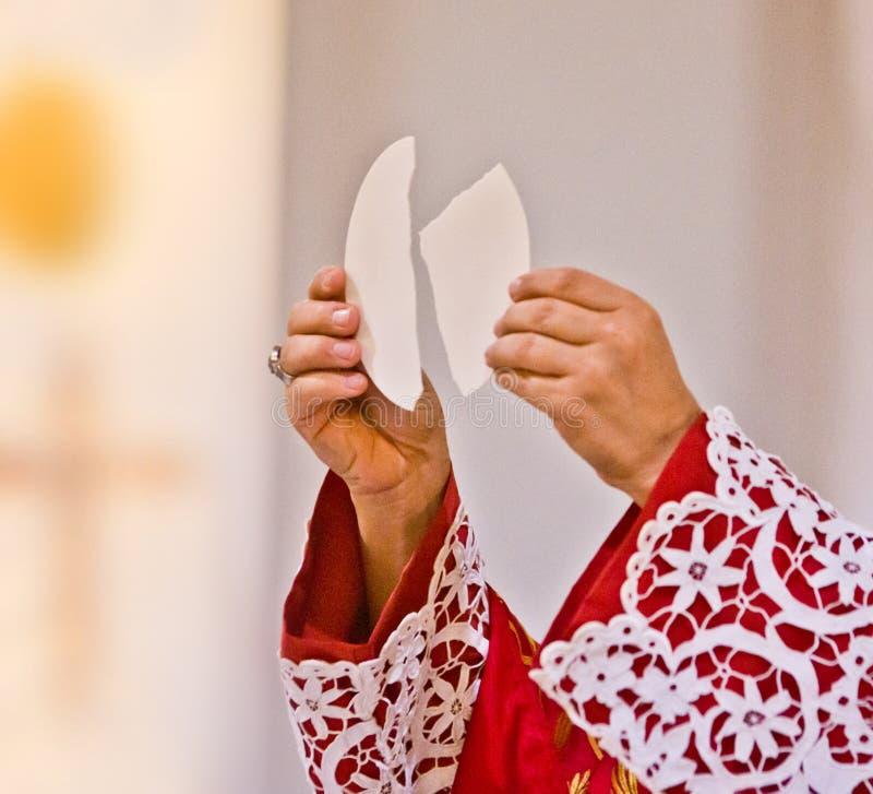 Las manos del sacerdote educan al cuerpo de Cristo imágenes de archivo libres de regalías