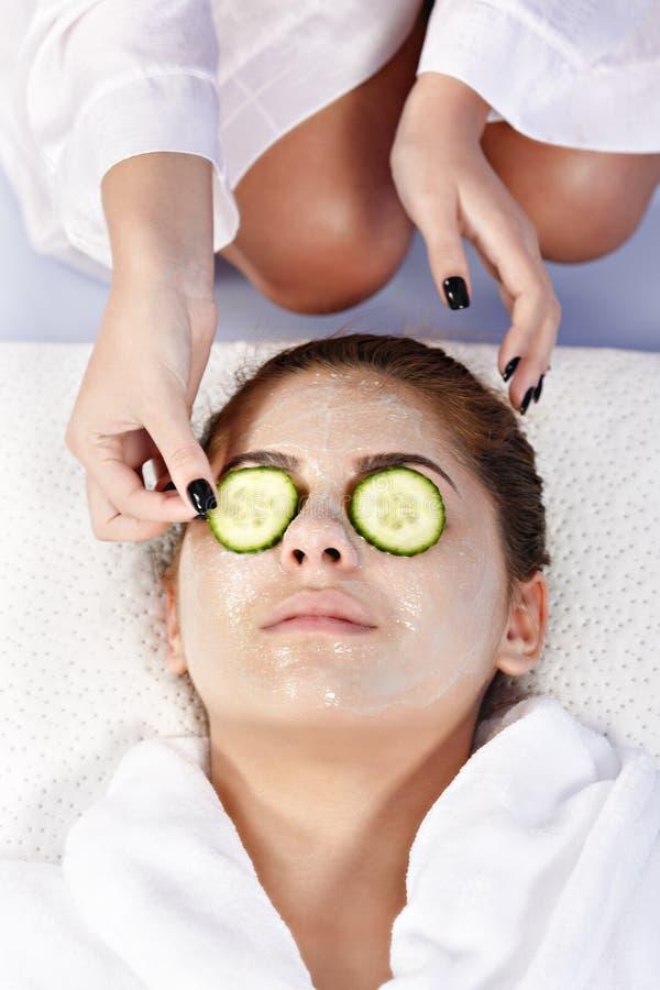 Las manos del terapeuta aplican la crema a la cara de la mujer Concepto de cuidado imagenes de archivo
