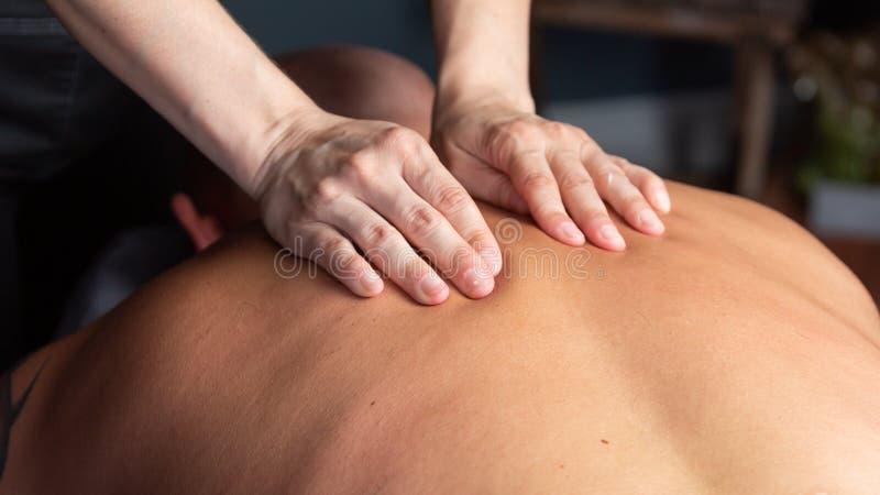 Las manos del terapeuta del masaje en la parte posterior de un hombre fotos de archivo libres de regalías