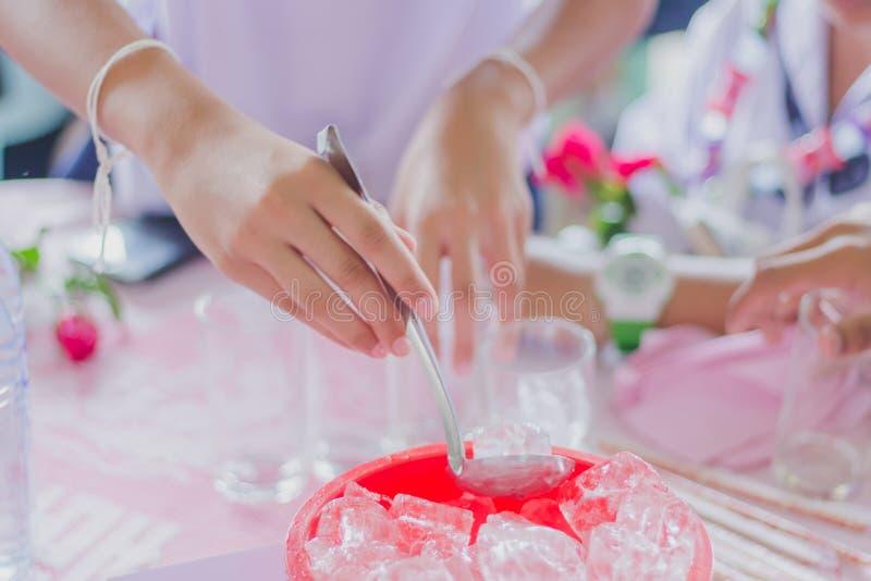 Las manos del th del primer añaden el hielo al vidrio para distribuir a los amigos fotos de archivo