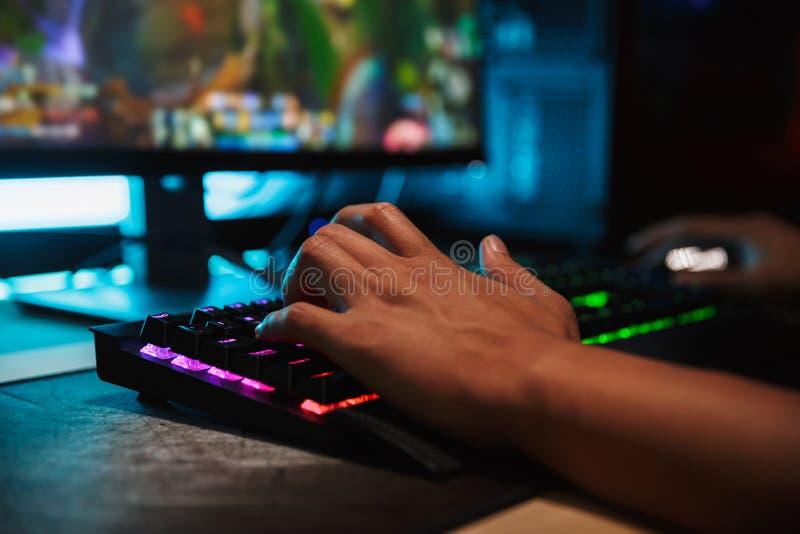Las manos del videojugador joven sirven jugar a los videojuegos en el ordenador en oscuridad foto de archivo libre de regalías